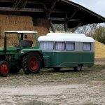 Das Bild zeigt einen Traktor mit angehängtem Wohnwagen.