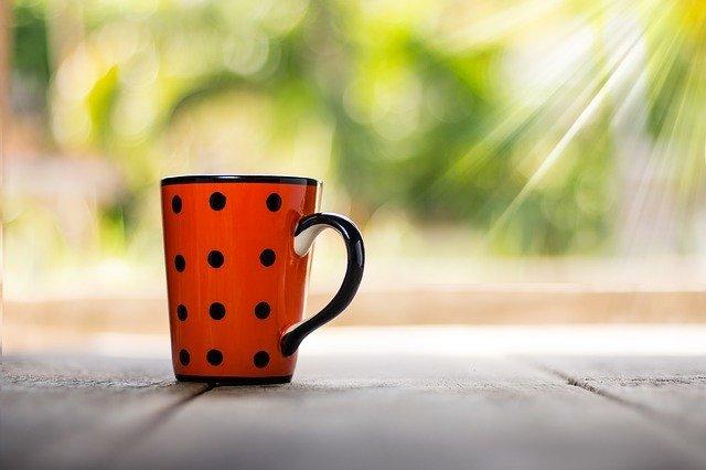 Das Bild zeigt eine Kaffeetasse auf einem Tisch.
