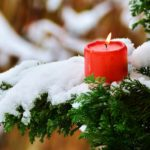 Das Bild zeigt einen verschneiten Tannenbaum mit einer Kerze.